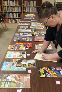 Academy Library Director Dr. Vandy Pacetti-Donelson inspects the tennis magazine collection that was recently donated to the American Sport Art Museum & Archives.